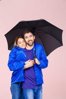 Hermosa joven pareja posando vistiendo una capa de lluvia con paraguas sobre pared rosa claro