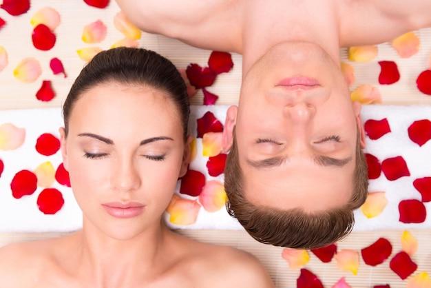 Hermosa joven pareja se relaja acostado en pétalos de rosa.
