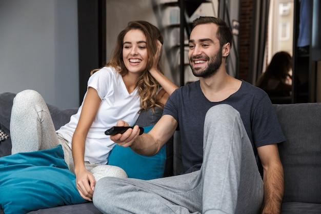 Hermosa joven pareja relajándose en un sofá en casa, viendo la televisión