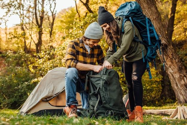 Hermosa joven pareja reúne sus mochilas en una caminata