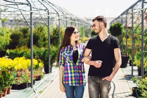 Hermosa joven pareja en ropa casual es elegir plantas y sonriendo