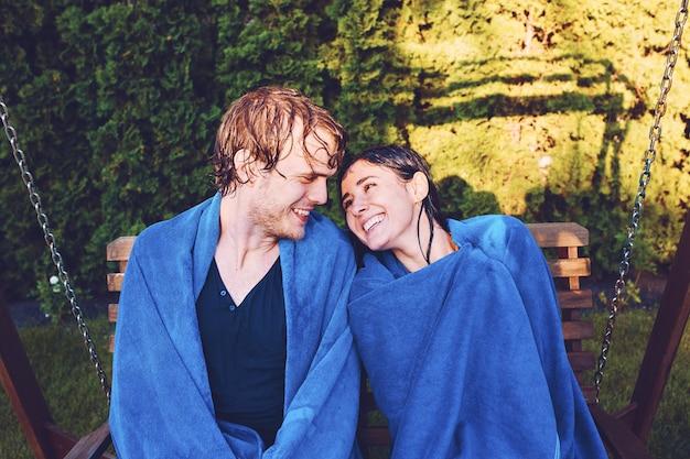 Hermosa joven pareja sentada en el banco junto a la piscina