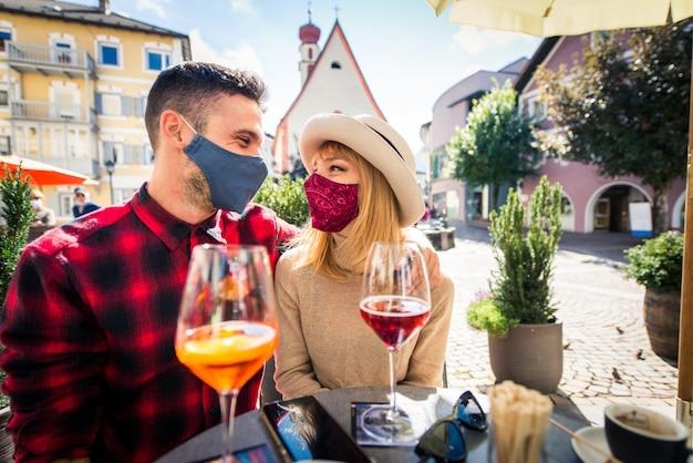 Hermosa joven pareja sentada en un bar restaurante y tomando una copa dos amantes que datan al aire libre