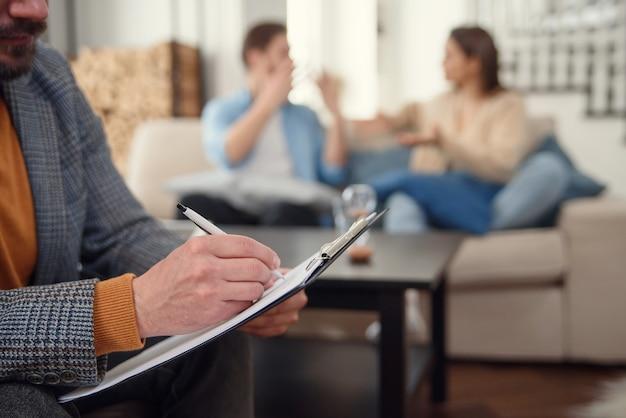 Hermosa joven pareja está sentada en el sofá y hablando con el psicólogo mientras el médico toma notas