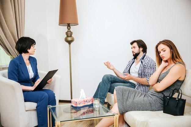 Hermosa joven pareja está sentada en el sofá. el hombre está hablando con el psicólogo. el doctor lo está escuchando. la niña está molesta.