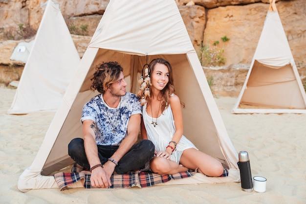 Hermosa joven pareja sentada en tipi en la playa