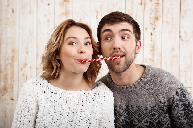 Hermosa joven pareja sonriendo comiendo dulces de navidad sobre pared de madera