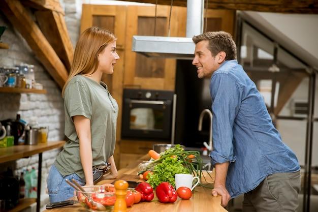 Hermosa joven pareja sonriendo mientras cocina en la cocina en casa