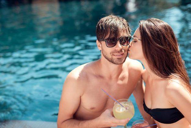 Hermosa joven pareja sosteniendo copas con alcohólico