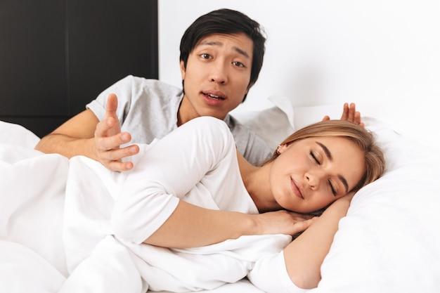 Hermosa joven pareja, tendido en la cama, hombre confundido mirando a la cámara