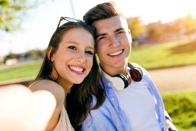 Hermosa joven pareja tomando un selfie en el parque.