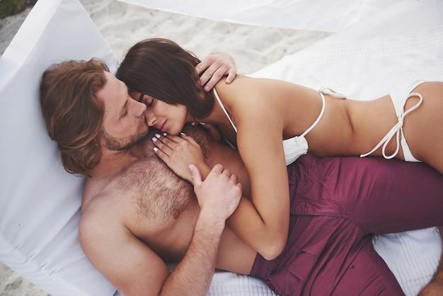 Hermosa joven pareja en traje de baño en la playa con una sonrisa de arena y un abrazo.