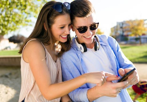 Hermosa joven pareja usando ellos teléfono móvil en el parque.