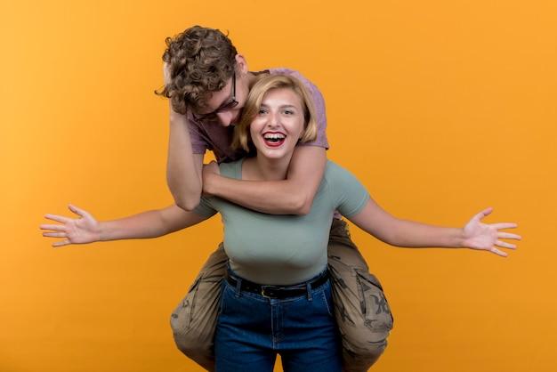 Hermosa joven pareja vistiendo ropa casual divirtiéndose juntos chica con su novio a cuestas de pie sobre la pared naranja