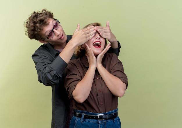 Hermosa joven pareja vistiendo ropa casual hombre feliz cerrando los ojos de su novia haciendo sorpresa sobre la luz