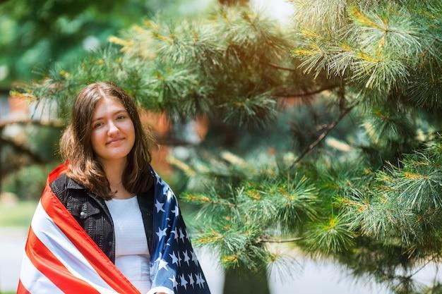 Hermosa joven patriótica con la bandera estadounidense en sus manos extendidas en pie el día de la independencia
