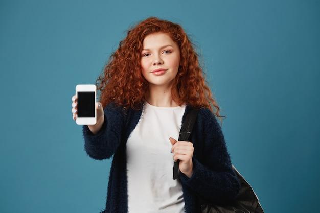 Hermosa joven pelirroja adolescente con pecas mostrando teléfono celular, sosteniendo la mochila con la mano, con una mirada feliz y confiada.