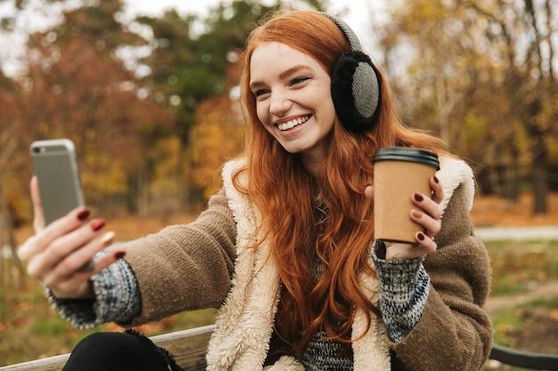Hermosa joven pelirroja escuchando música con headpones mientras está sentado en un banco, tomando un selfie