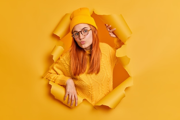 Hermosa joven pelirroja con labios redondos vestida con sombrero y suéter tiene expresión de coqueteo vestida con ropa amarilla se encuentra a través de papel rasgado