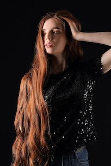 Hermosa joven pelirroja sobre fondo oscuro