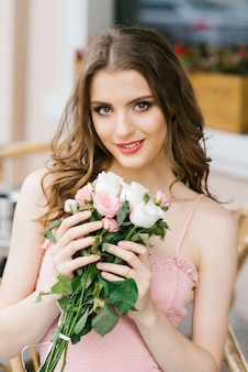 Hermosa joven de pelo castaño con un ramo de rosas, maquillaje profesional y peinado.