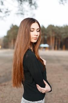 Hermosa joven con el pelo largo en camisa negra