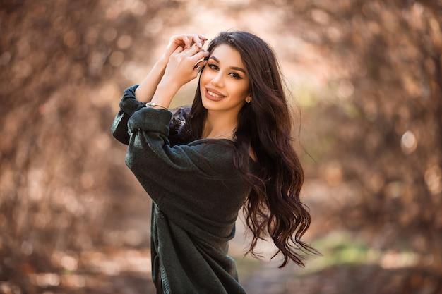 Hermosa joven con el pelo largo en un paseo por el bosque de otoño