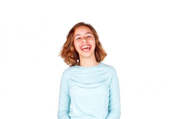 Hermosa joven con el pelo rizado loco se ríe con la boca abierta