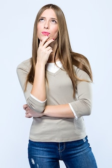 Hermosa joven pensando sobre fondo blanco.