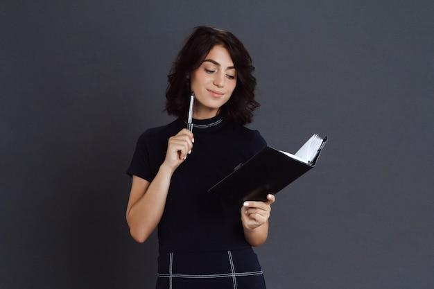 Hermosa joven pensativa posando sobre pared gris y sosteniendo el cuaderno en las manos
