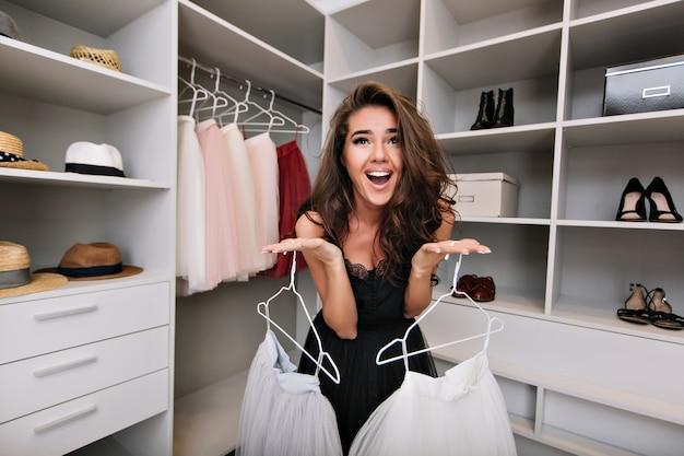 Hermosa joven pide ayuda para elegir la ropa en un vestidor. está vestida de negro. expresando verdaderas emociones positivas faciales.