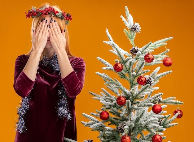 Hermosa joven de pie cerca del árbol de navidad con vestido rojo y corona con guirnalda en el cuello cubierto rostro con manos aisladas sobre fondo naranja