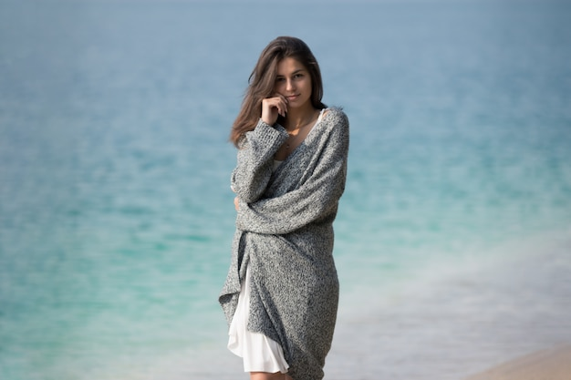 Hermosa joven de pie junto al lago. retrato de estilo de vida en la naturaleza.