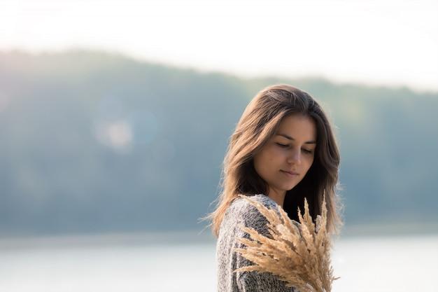Hermosa joven de pie junto al lago.