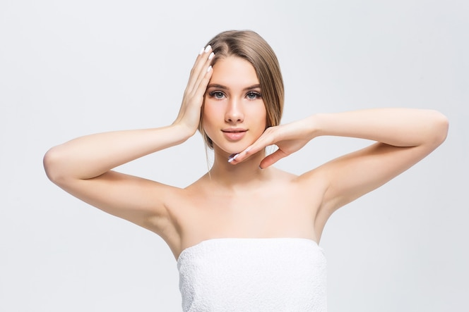 Hermosa joven con piel suave en una pared clara con maquillaje natural