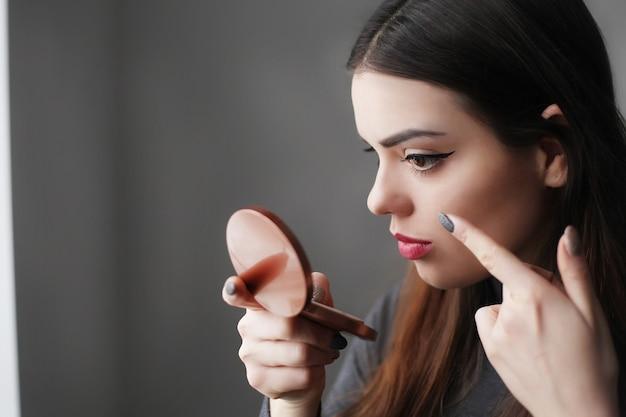 Hermosa joven poniendo lápiz labial en los labios