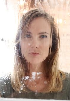 Hermosa joven posando detrás de la ventana mojada