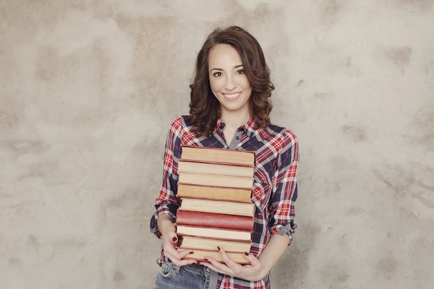 Hermosa joven posando con libros