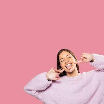 Hermosa joven posando con papel tapiz rosa en la espalda