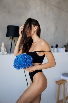 Hermosa joven posando en ropa interior en la sala de estar. modelo de retrato de moda en salón con flores azules.