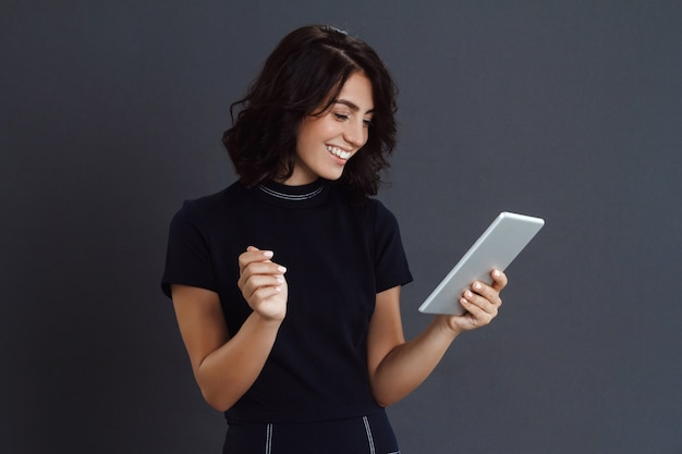 Hermosa joven posando sobre pared gris y sosteniendo la tableta en manos
