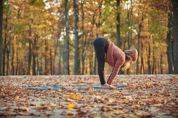 Hermosa joven practica yoga asana ardha uttanasana - pose de plegado hacia adelante medio de pie en la cubierta de madera en el parque de otoño.