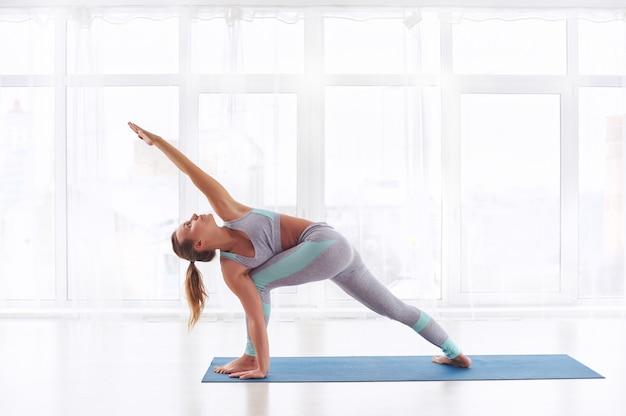 Hermosa joven practica yoga asana parivritta parshvakonasana - postura de ángulo lateral giratorio en el estudio de yoga