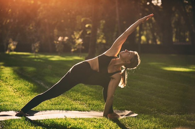 Hermosa joven practica yoga asana parivritta parshvakonasana - postura de ángulo lateral giratorio en el parque