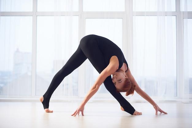 Hermosa joven practica yoga asana parivritta trikonasana en el estudio de yoga