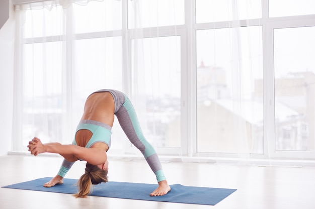 Hermosa joven practica yoga asana prasarita padottanasana en la clase de yoga