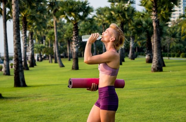 Hermosa joven practica yoga en la playa. ejercicio temprano en la mañana. agua potable. amanecer