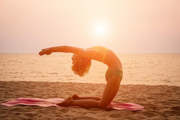 Hermosa joven practica yoga en la playa. ejercicio temprano en la mañana