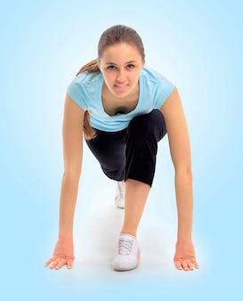 Una hermosa joven practicando deportes sobre un fondo azul.