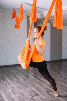 Hermosa joven practicando yoga aéreo en el gimnasio